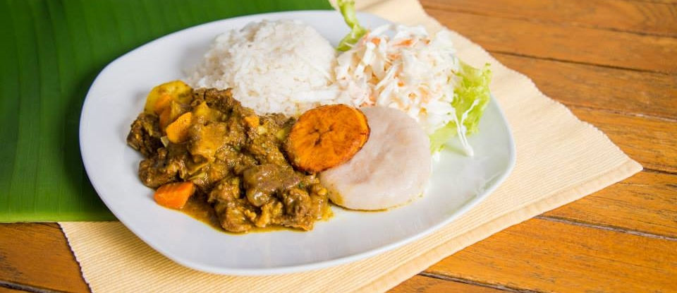 Curry Goat served with white rice, cole slaw, plantain and dumpling