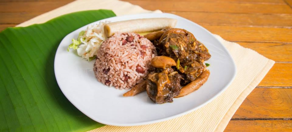 Oxtail with broad beans served with rice and peas, cole slaw and boiled green banana